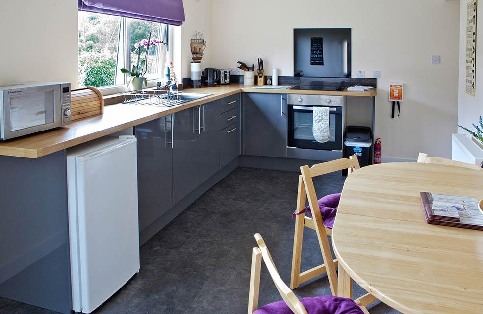 сиреневая-кухня-с-деревянными-стульями